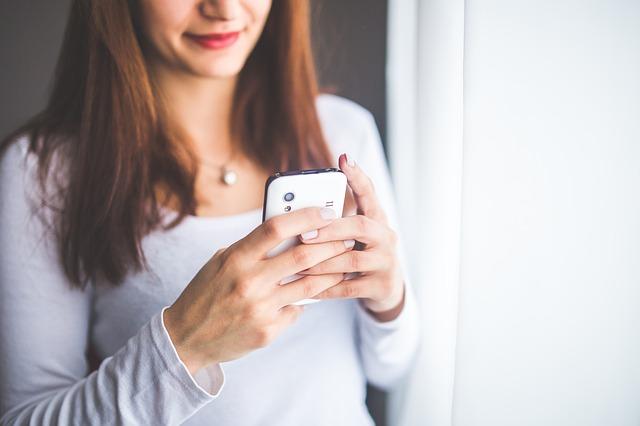 スマホを触っている女性の画像